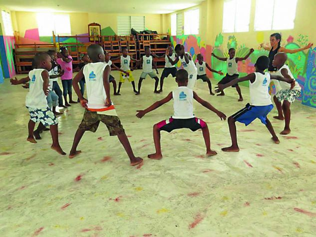 Children practicing Capoeira, which combines elements of dance, acrobatics and music