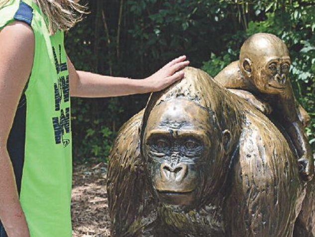 A child touches the head of a gorilla statue in Cincinnati Zoo