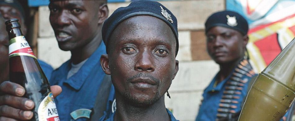 Burundi, A police officer poses with a beer