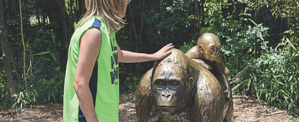 A child touches the head of a gorilla statue in Cincinnati Zoo